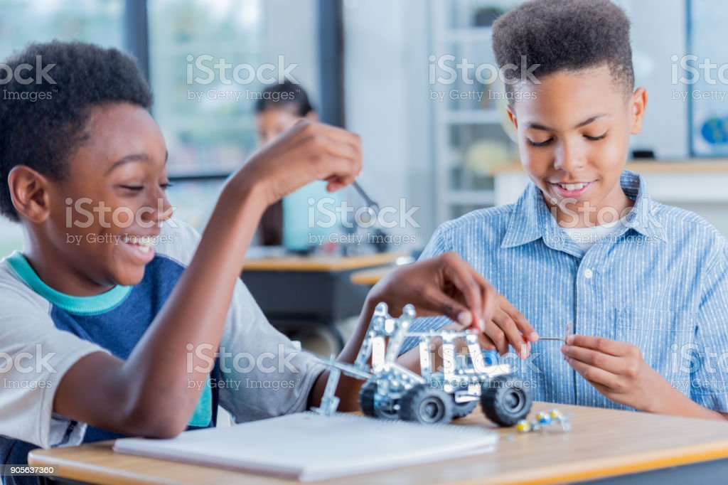 Two preteen boys work on robotics project together at school stock photo
