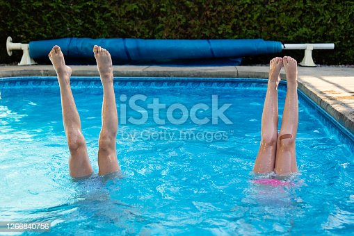 Two preteen girl's leg standing up in a pool. Playful candid outdoors summer shot. Horizontal waist up with copy space.
