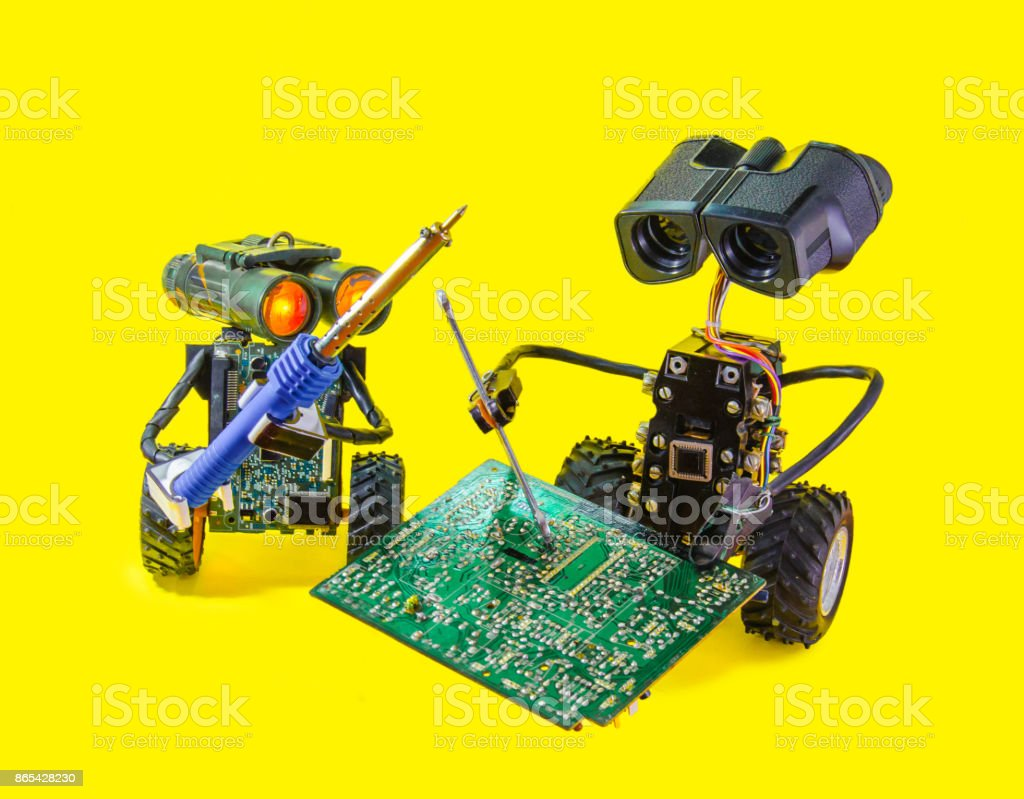 Two Pretty Cheerful Robot Repair Printed Circuit Board With Soldering Iron Royalty Free Stock Photo