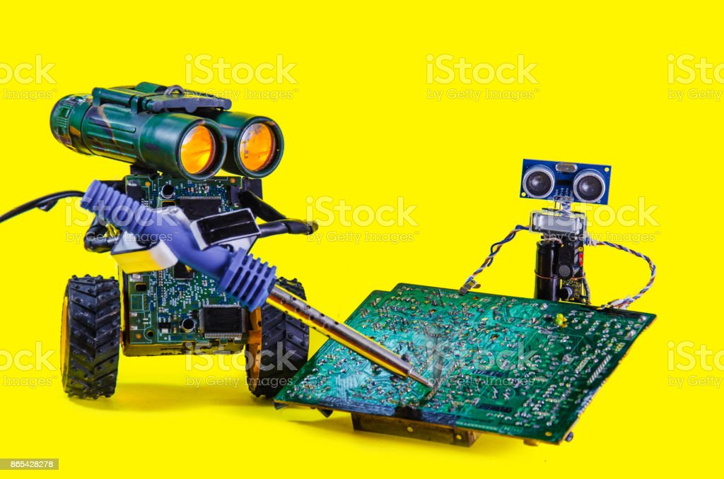 Two pretty cheerful robot repair printed circuit board with soldering...