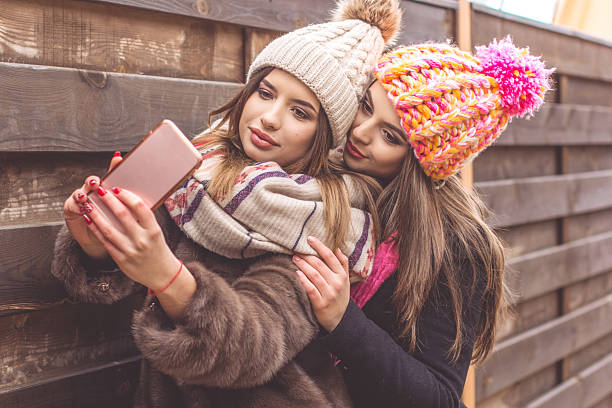 two pretty girl are taking selfie with smartphone - wintermantel damen wolle stock-fotos und bilder