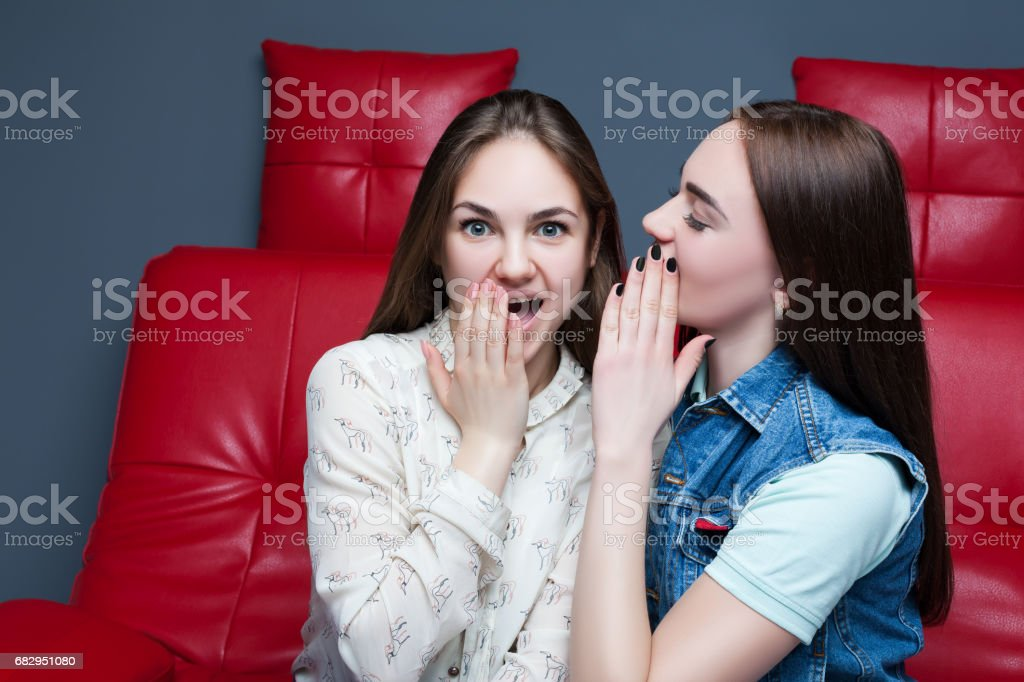 Two pretty girls gossiping on red leather couch royalty-free stock photo
