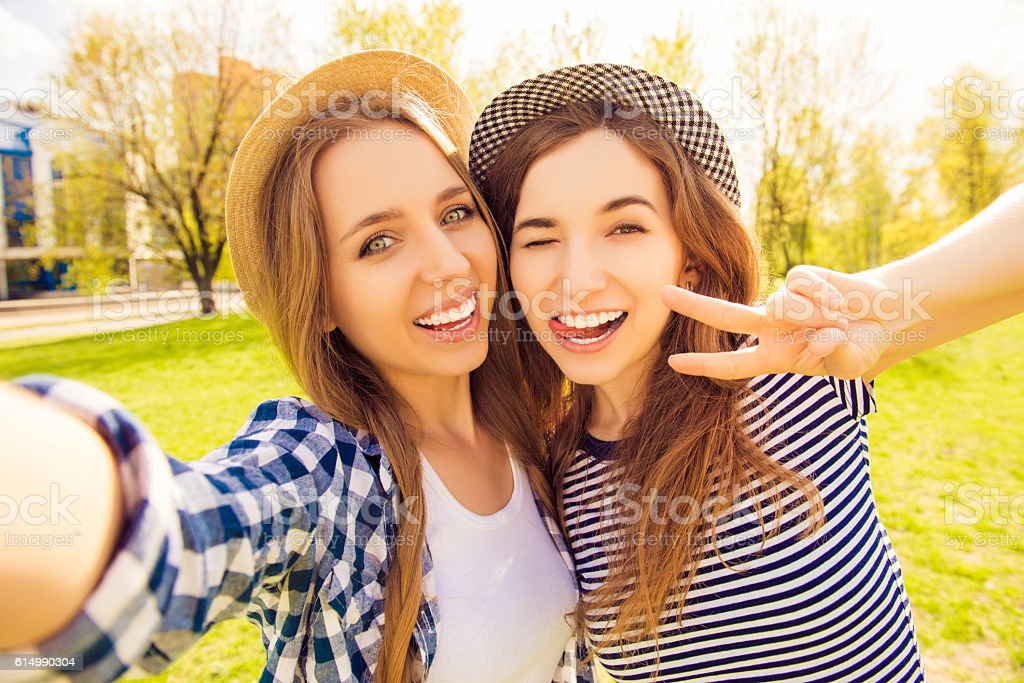 Two pretty girls making selfie and smiling - Photo