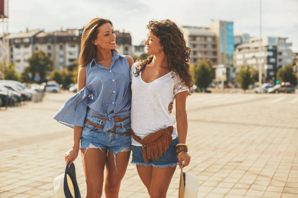 two pretty girls on city street - jean shorts stock photos and pictures