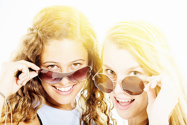 Two pretty girls peep flirtatiously from behind sunglasses, smiling Two pretty, smiling young women checking things - or boys - out from behind their sunglasses. dazzled stock pictures, royalty-free photos & images
