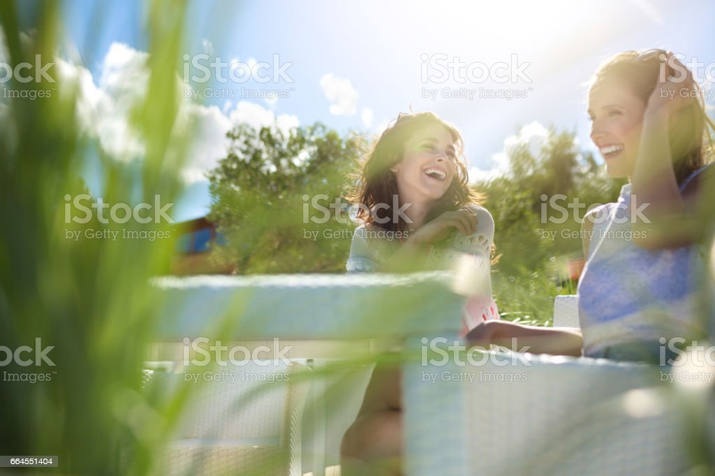 Two pretty girls sitting at cafe table laughing royalty-free stock photo