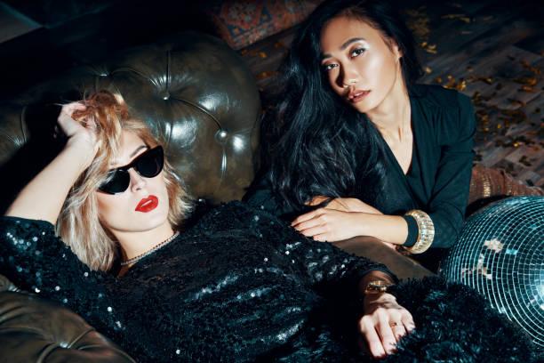 Zwei hübsche multiethnische junge Frauen entspannt nach der Party – Foto