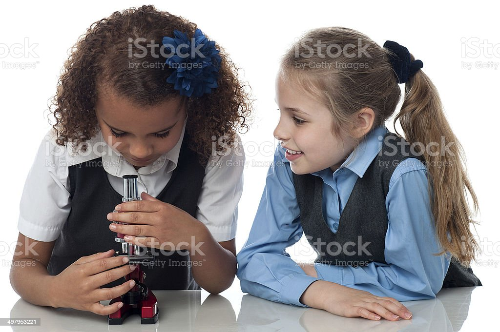 Two pretty school girls with microscope stock photo
