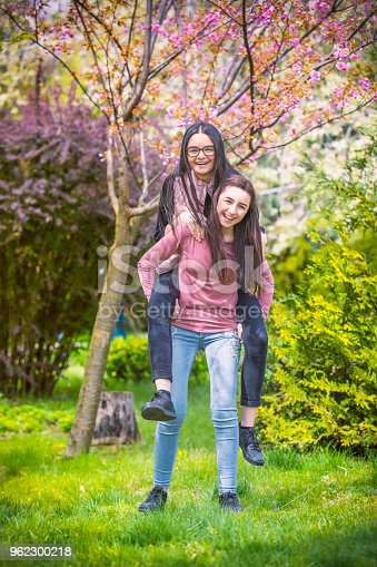 1092709104 istock photo Two pretty sisters girls having fun together 962300218