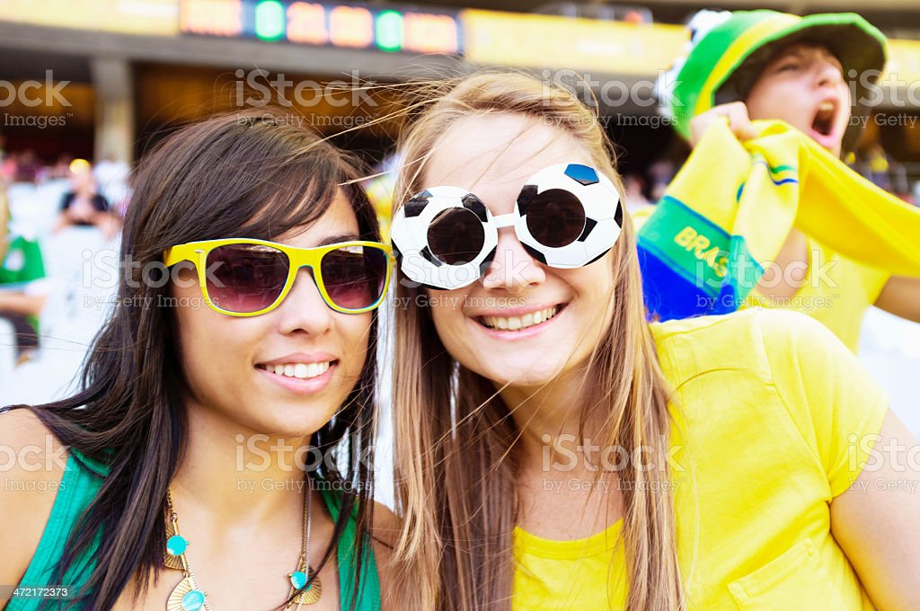 Two pretty soccer fans in Brazilian team colors at match stock photo