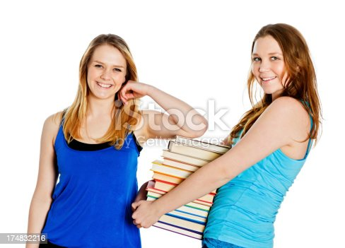 639569206 istock photo Two pretty teenage students with a large stack of books 174832216