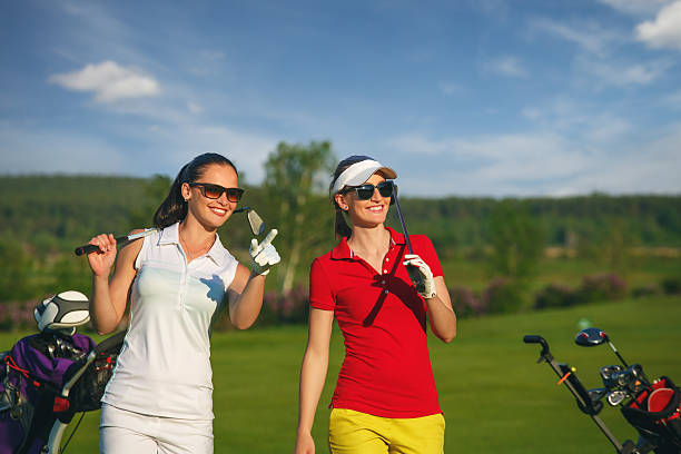 Two pretty women golfers walking at golf course stock photo