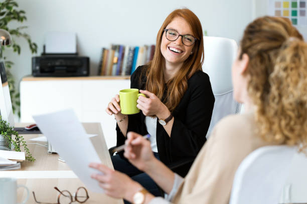 two pretty young business woman relaxing one moment while drinking coffee in the office. - collega foto e immagini stock