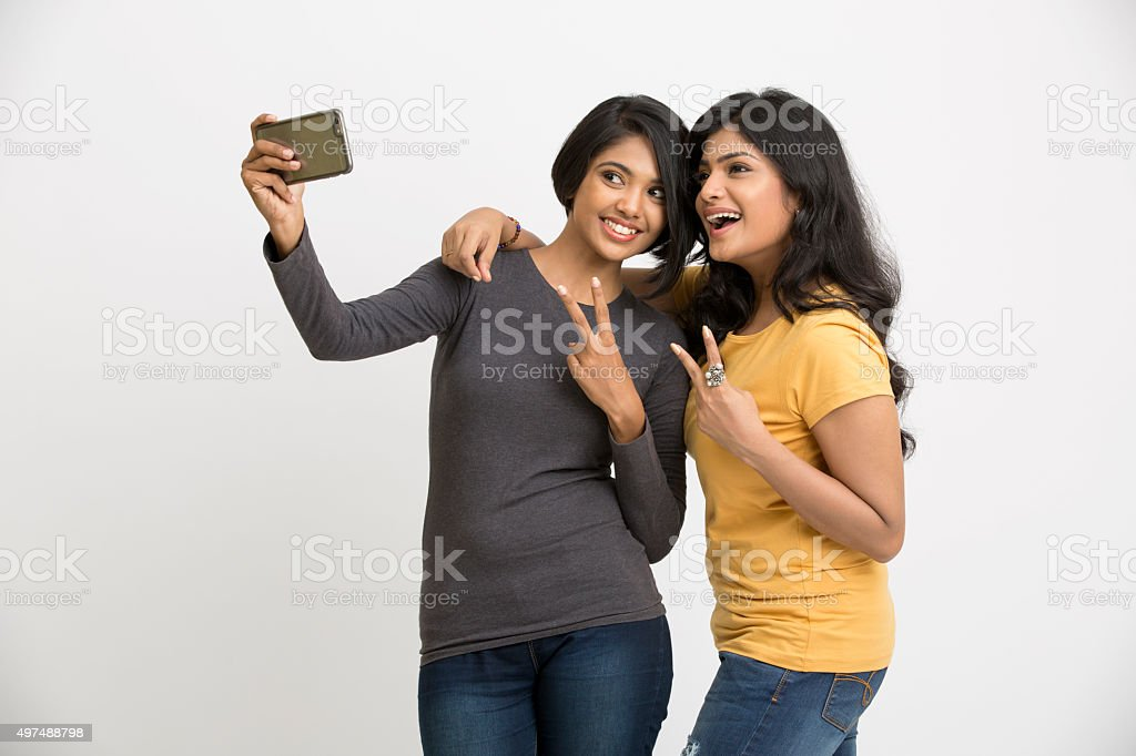 Two pretty young women taking selfie with mobile phone stock photo