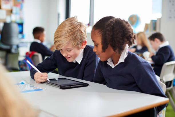 dos niños de escuela primaria sentados juntos en el escritorio en un aula con una computadora de la tableta y un lápiz, de cerca - escuela primaria fotografías e imágenes de stock