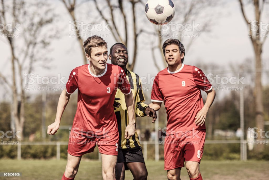 Two professional adult soccer teams competing for the ball during a...