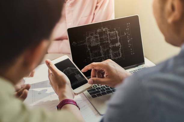 Two professional architects discussing house building plan design project with looking blueprints in computer and phone at desk in office. stock photo