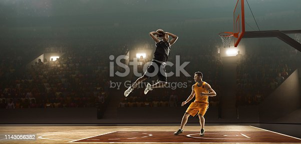 Two professional basketball players on a professional sports arena fight fo a ball. One of the players scores