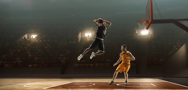 Two professional basketball players fight fo a ball Two professional basketball players on a professional sports arena fight fo a ball. One of the players scores basketball ball stock pictures, royalty-free photos & images
