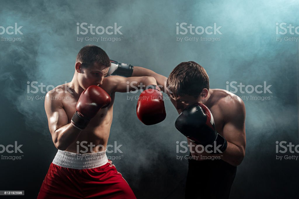 Two professional boxer boxing on black smoky background stock photo