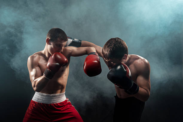 Cтоковое фото Two professional boxer boxing on black smoky background