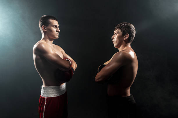 Two professional boxer standing on black smoky background stock photo
