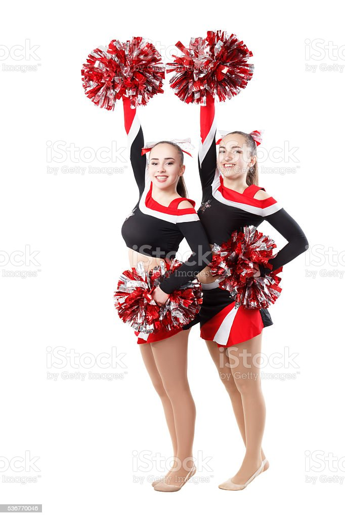 Two professional cheerleaders posing at studio. Hands raised up. stock photo