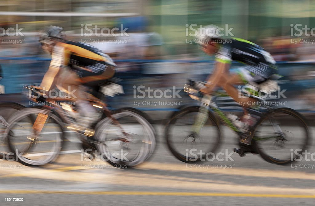 Two professional Cyclists and a blur of spectators royalty-free stock photo