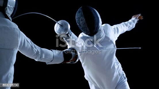 istock Two Professional Fencers Show Masterful Swordsmanship in their Foil Fight. They Attack, Defend, Leap and Thrust and Lunge. Shot Isolated on Black Background. 853233230
