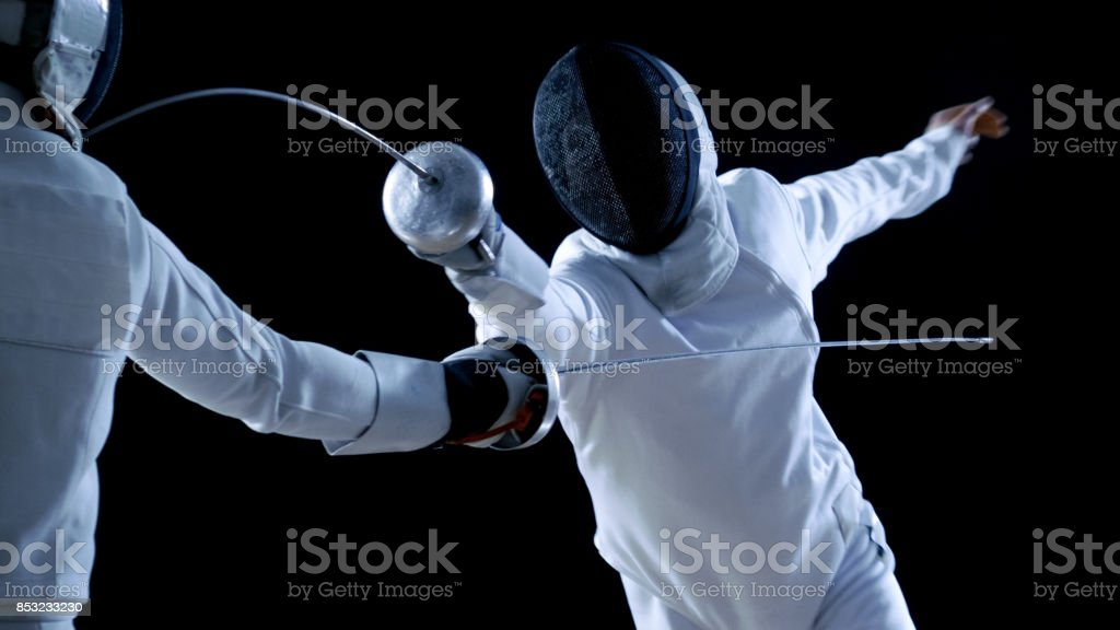 Two Professional Fencers Show Masterful Swordsmanship in their Foil Fight. They Attack, Defend, Leap and Thrust and Lunge. Shot Isolated on Black Background. stock photo