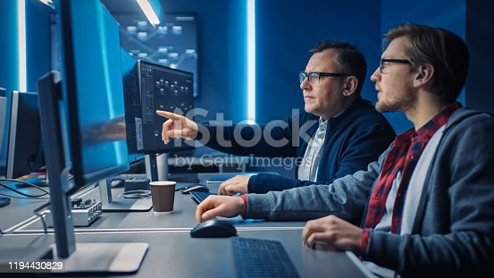 1154261912 istock photo Two Professional IT Programers Discussing Blockchain Data Network Architecture Design and Development Shown on Desktop Computer Display. Working Data Center Technical Department with Server Racks 1194430829