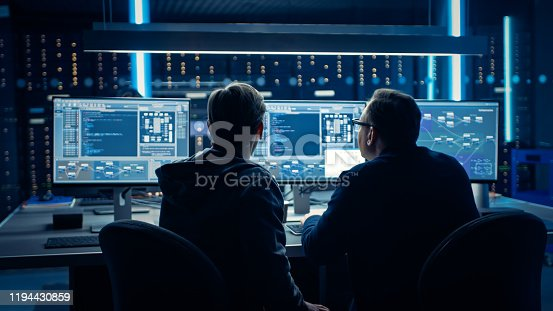 istock Two Professional IT Programers Discussing Blockchain Data Network Architecture Design and Development Shown on Desktop Computer Display. Working Data Center Technical Department with Server Racks 1194430859