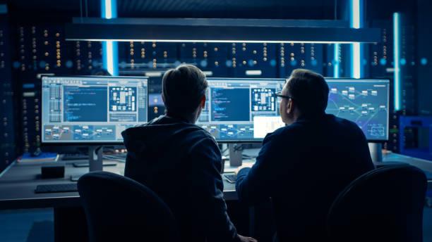 Zwei professionelle IT-Programmierer, die das Design und die Entwicklung von Blockchain Data Network Architecture auf Desktop-Computern diskutieren. Technische Abteilung für Arbeitsdatenzentren mit Server-Racks – Foto
