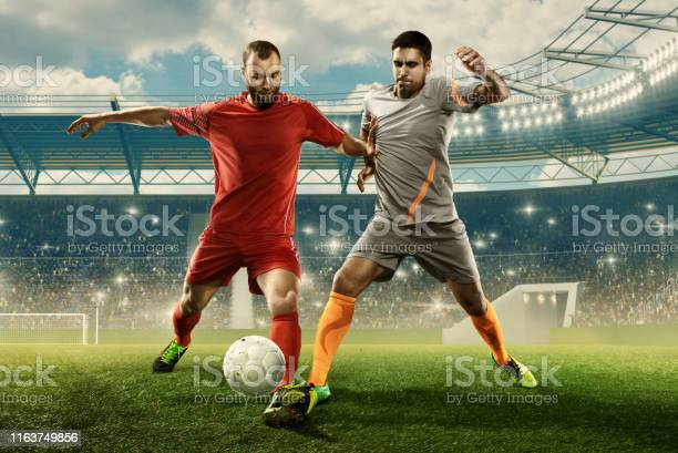 Two professional soccer players fight for a ball on a stadium picture id1163749856?b=1&k=6&m=1163749856&s=612x612&h=v2gog2aqtnbw3wxt6keejheph zkxjlq9t3alb2kxrs=