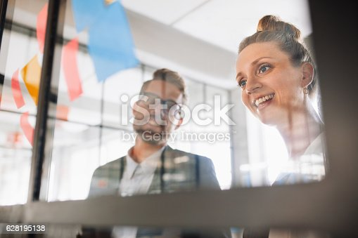 496441730 istock photo Two professionals looking over adhesive notes 628195138