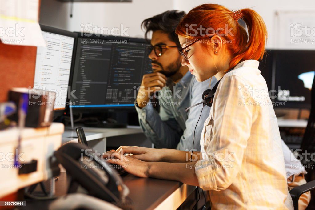 Two programmers working on new project.They working late at night at the office. - Royalty-free Adult Stock Photo