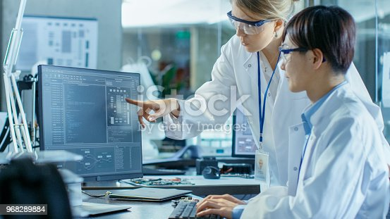 921019684istockphoto Two Prominent Computer Engineers Working with Programming Software on Personal Computer. In the Background Scientifically Advanced Research Center. 968289884