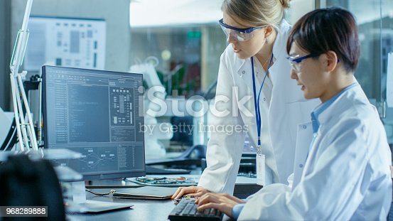 921019684istockphoto Two Prominent Computer Engineers Working with Programming Software on Personal Computer. In the Background Scientifically Advanced Research Center. 968289888