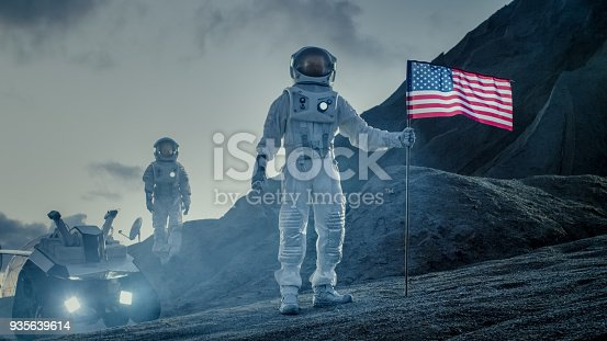istock Two Proud Astronauts Plant American Flag on the Alien Planet. In the Background Research Base and Rover. 935639614