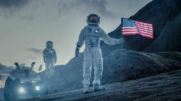 two proud astronauts plant american flag on the alien planet. in the background research base and rover. - astronaut stock pictures, royalty-free photos & images