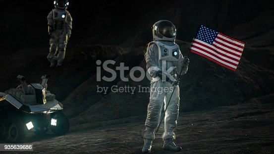 istock Two Proud Astronauts Plant American Flag on the Alien Planet. In the Background Research Base and Rover. 935639686