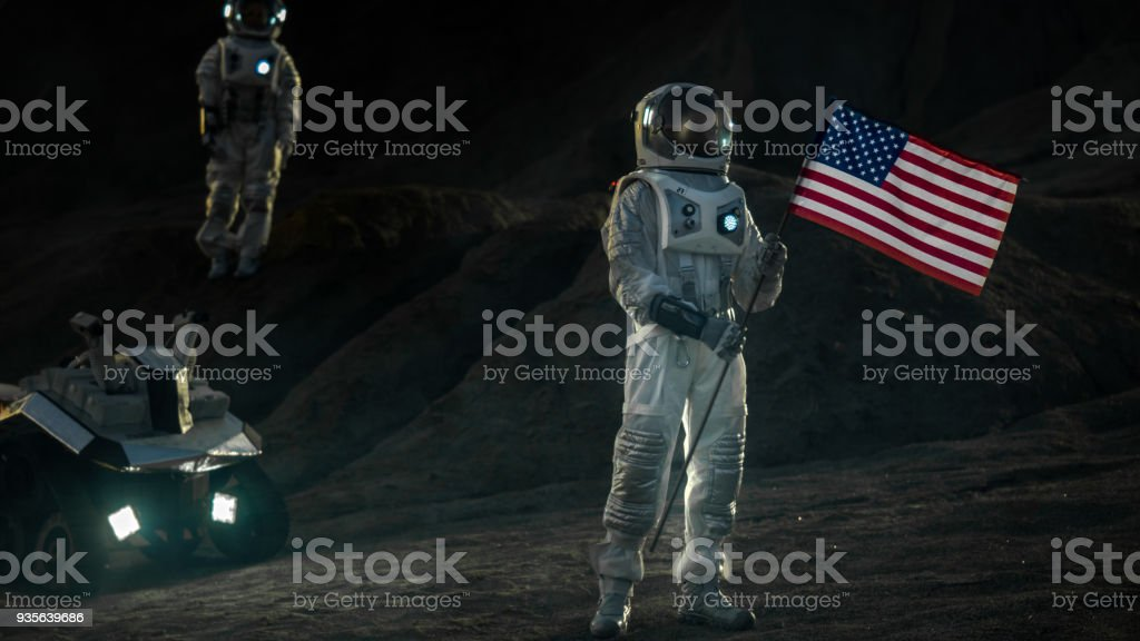 Two Proud Astronauts Plant American Flag on the Alien Planet. In the Background Research Base and Rover. stock photo