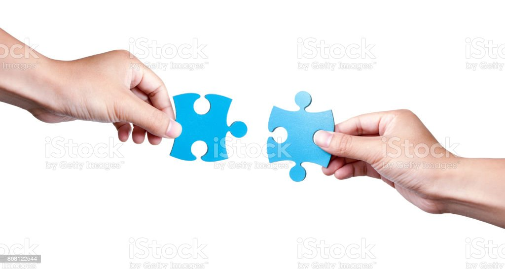 Two Puzzle Pieces Coming Together isolated on white background stock photo