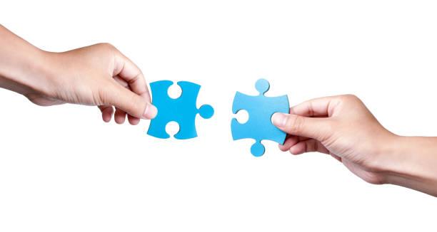 zwei puzzle-stücke coming together isoliert auf weißem hintergrund - puzzleteile stock-fotos und bilder
