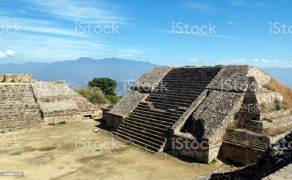 Two pyramids (one complete, one half) in ruins on a sunny day with hilly background stock photo