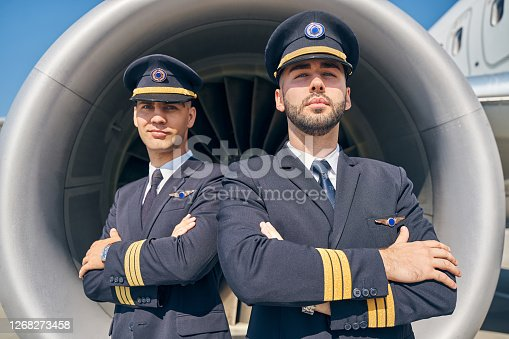 Waist-up portrait of calm young men in uniforms standing in front of the turbofan engine