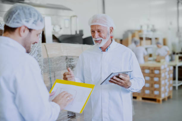 Two quality control workers in sterile white uniforms comparing data. Older one holding tablet while younger one looking at chart. Two quality control workers in sterile white uniforms comparing data. Older one holding tablet while younger one looking at chart. food warehouse stock pictures, royalty-free photos & images
