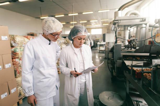 zwei qualitätsfachleute in weiß sterilen uniformen überprüfen die qualität von salzstäben, während sie in der lebensmittelfabrik stehen. - nahrungsmittelfabrik stock-fotos und bilder
