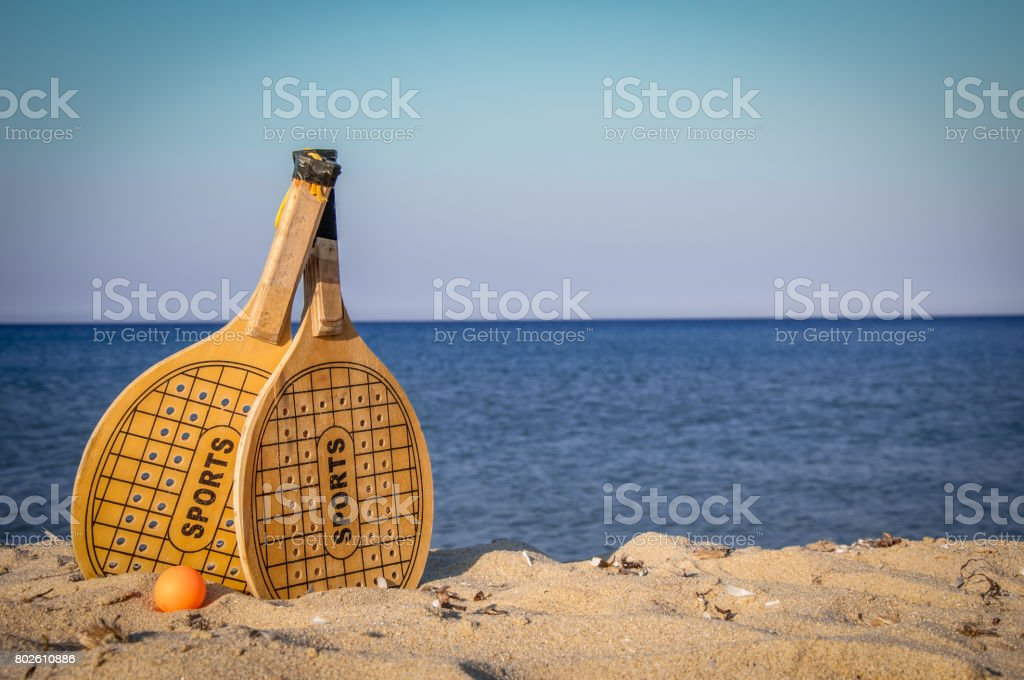 Two rackets and a ball in the beach - foto stock
