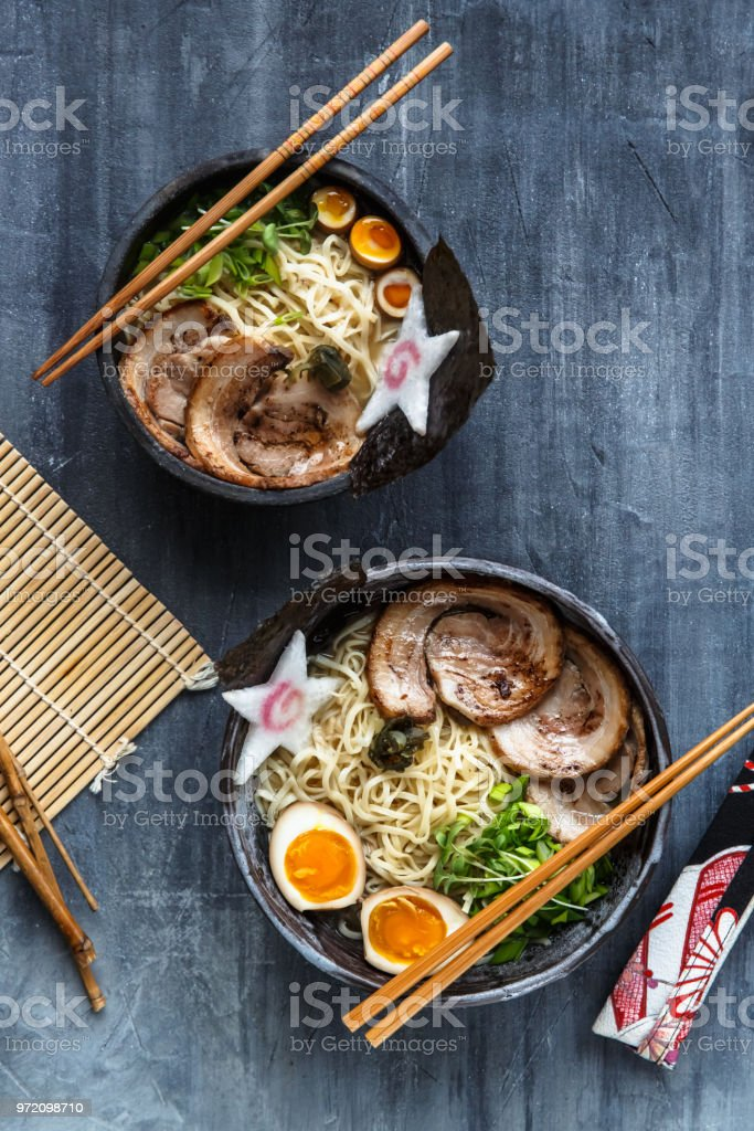 Two ramen bowls with pork, egg and chives, top view stock photo
